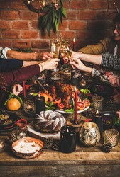Family celebrating Christmas or New Year. People clinking glasses of champagne over holiday wooden table with roasted turkey, chocolate cake and candles, red brick wall at background