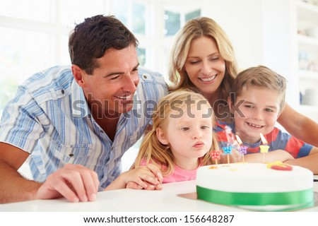 Family Celebrating Daughters Birthday With Cake