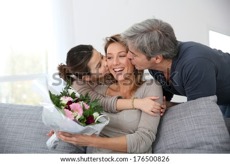 Family celebrating mother\'s day with bunch of flowers