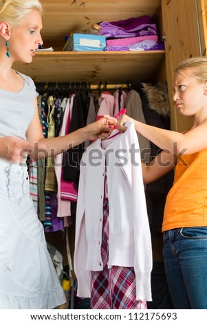 Family - child and mother in front of closet or wardrobe, teenager should put on a dress but does not like it
