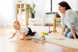 family, child and motherhood concept - happy mother with little baby boy and developmental toys at home