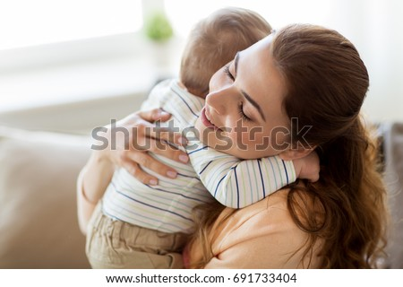 family, child and motherhood concept - happy smiling young mother hugging little baby at home
