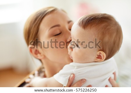 family, child and parenthood concept - close up of happy smiling young mother kissing little baby at home