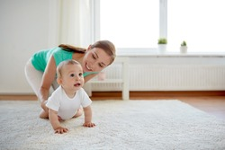 family, child and parenthood concept - happy smiling young mother playing with little baby at home