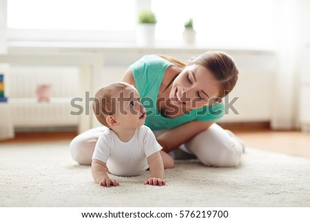 family, child and parenthood concept - happy smiling young mother playing with little baby at home #576219700