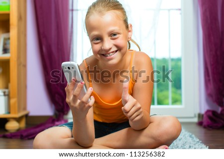 Family - child with cell or smartphone at home in the living room
