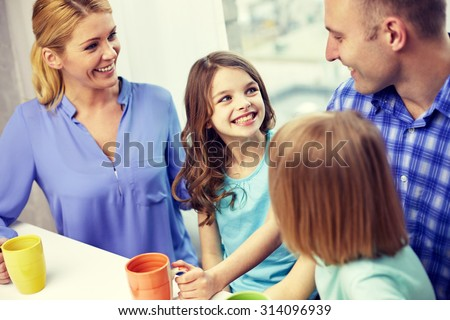 family, childhood, breakfast and people - happy parents and children drinking tea with cups at home