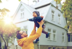 family, childhood, fatherhood, leisure and people concept - happy father and little son playing and having fun outdoors over living house background
