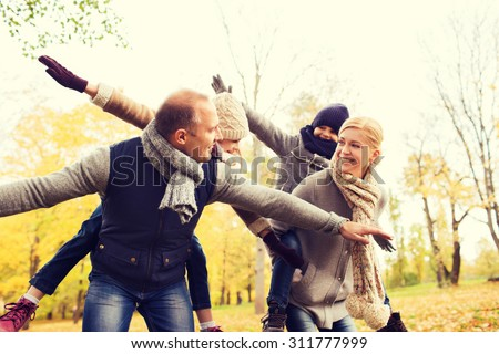 family childhood season and people concept happy family having fun in autumn park