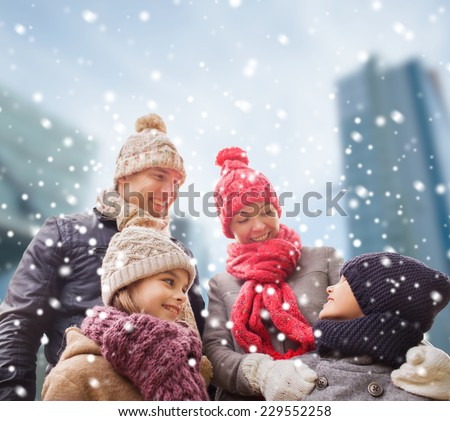 family, childhood, season and people concept - happy family in winter clothes over snowy city background