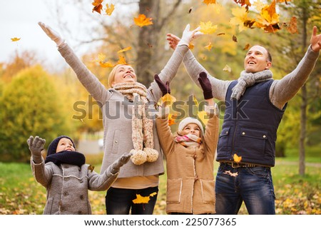 family childhood season and people concept happy family playing with autumn leaves in park