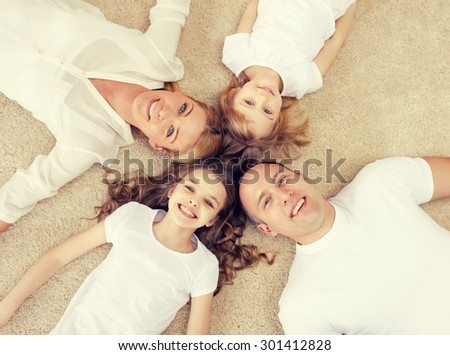 family, children and home concept - smiling family with and two little girls lying in circle on floor at home