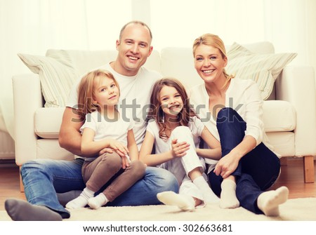 family, children and home concept - smiling family with and two little girls sitting on floor at home