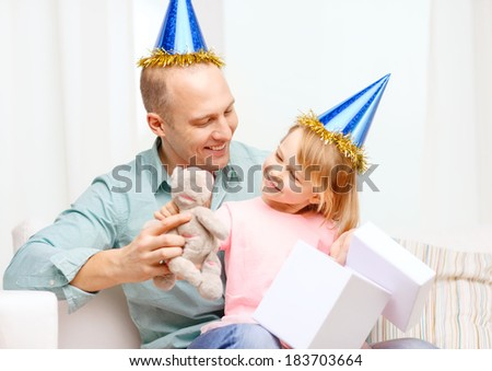 family, children, celebration, holidays, birthday and happy people concept - happy father and daughter in blue party hats with gift box