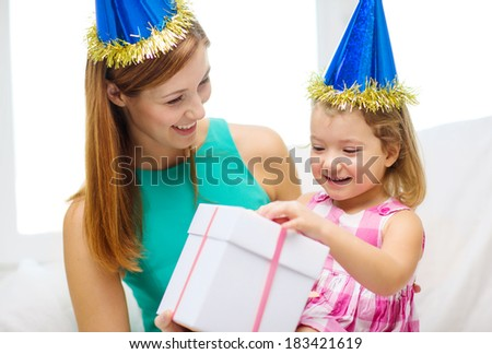 family, children, celebration, holidays, birthday and happy people concept - happy mother and daughter in blue party hats with gift box
