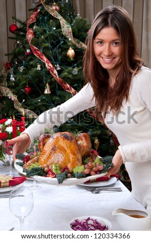Family christmas dinner celebration. Woman holding Roasted turkey, red candles, fir tree ornament decoration, rich table with meals. Focus on turkey