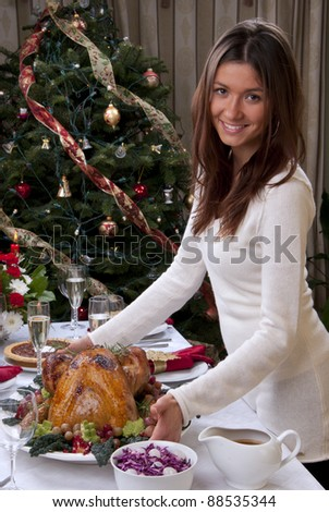 Family christmas dinner celebration. Woman holding Roasted turkey, red candles, fir tree ornament decoration, rich table with meals, champagne glasses, pie, grapes and vegetables