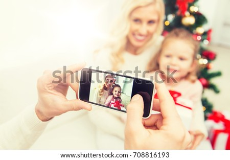 family, christmas, technology and people concept - close up of man taking picture of his family by smatrphone