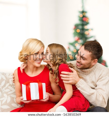 family, christmas, x-mas, winter, happiness and people concept - adorable child kisses her mother and gives present