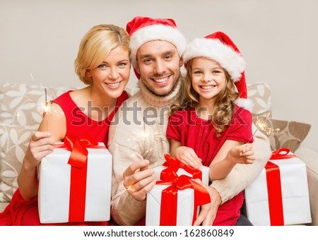 family christmas x-mas winter happiness and people concept smiling family in santa helper hats with many gift boxes and bengal lights
