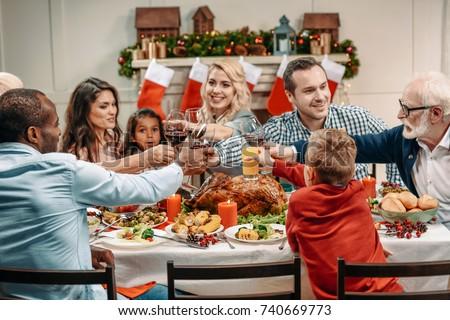 family clinking glasses while having christmas dinner #740669773