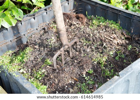 Family compost with a fork to turn it around #614614985