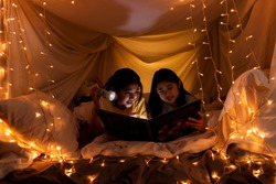 Family concept. elder sister and sister reading book with flashlight together in children tent before bedtime. Happy elder sister read story book to her sister in bed sheet tent