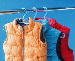 family concept of down vest jackets hanging on a hanger in the wardrobe