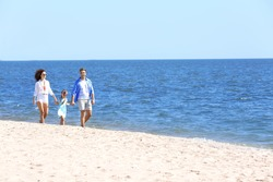 Family concept. Parents with daughter holding hands and walking on sea shore
