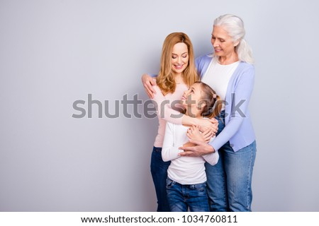 Family concept. Portrait of adorable lovely cute family generation standing hugging together wearing casual clothed isolated on gray background copyspace #1034760811