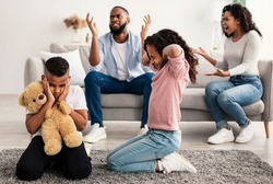 Family Conflicts. Sad little black children covering ears with hands while their parents arguing in the background, upset boy and girl don't want to hear quarrel, stressed kid sitting on the floor