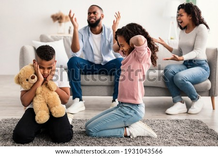 Family Conflicts. Sad little black children covering ears with hands while their parents arguing in the background, upset boy and girl don't want to hear quarrel, stressed kid sitting on the floor Stock photo ©