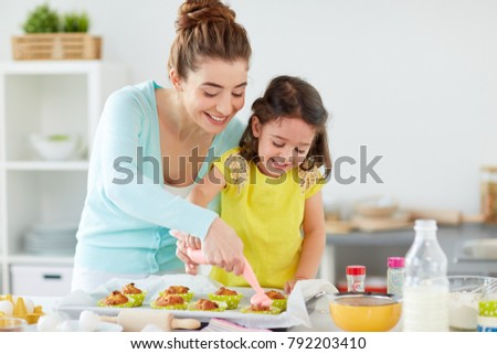 family, cooking and people concept - mother and little daughter making and decorating cupcakes with cream frosting at home kitchen