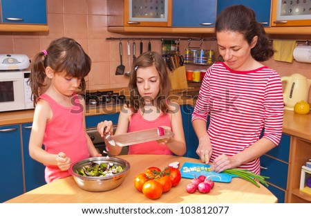 Family cooking at home. Happy smiling mother with kids cook healthy food together at kitchen. Family preparing salad