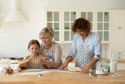 Family cooking. 3 generations women prepare bakery at home kitchen. Young female mom roll dough while elderly aged grandma teach little girl grandkid daughter press cookies using diverse metal cutters