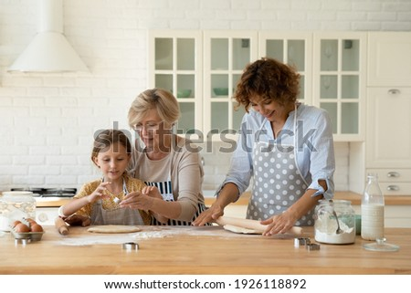 Family cooking. 3 generations women prepare bakery at home kitchen. Young female mom roll dough while elderly aged grandma teach little girl grandkid daughter press cookies using diverse metal cutters Сток-фото ©