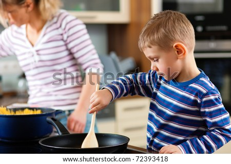 Family cooking in their kitchen � mother and sun cooking spaghetti