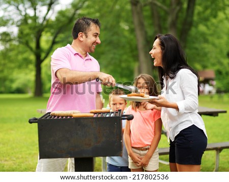 family cookout - dad giving mom food on platter from grill