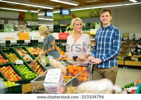 Family couple buying sweet fruits in local food shop