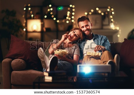 Family couple watching television projector at home on the sofa Foto stock ©
