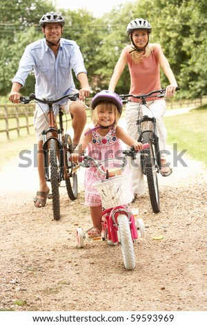 Family Cycling In Countryside Wearing Safety Helmets