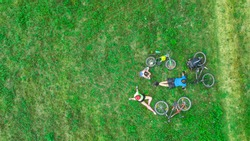 Family cycling on bikes outdoors aerial view from above, happy active parents with child have fun and relax on grass, family sport and fitness