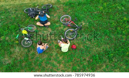 Family cycling on bikes outdoors aerial view from above, happy active parents with child have fun and relax on grass, family sport and fitness on weekend  #785974936