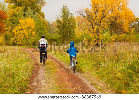 Family cycling outdoors, beautiful golden autumn in park