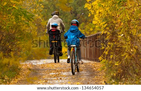 Family cycling outdoors, father and kids on bikes, golden autumn in park