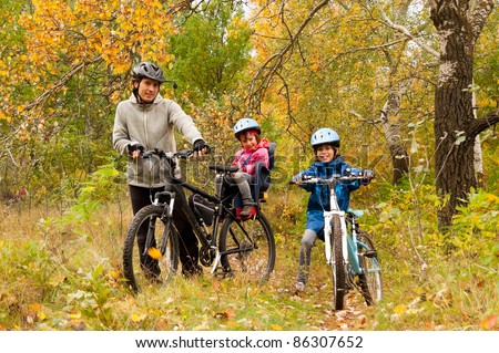 Family cycling outdoors, golden autumn in park