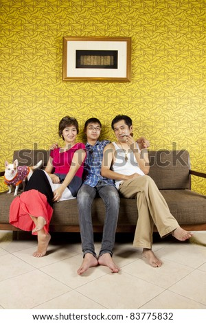 family day, three person of family portrait funny on a sofa in yellow room.