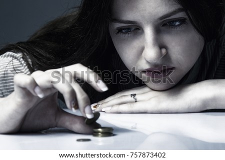 Family debts. Young frustrated and desperate Woman counting small money (Bankrupt, poverty, tax, money concept) Stock photo ©