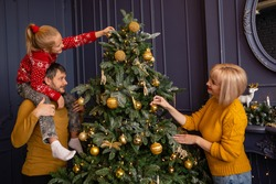 Family decorates a Christmas tree on new year eve.