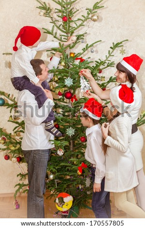 Family decorates at Christmas tree at home